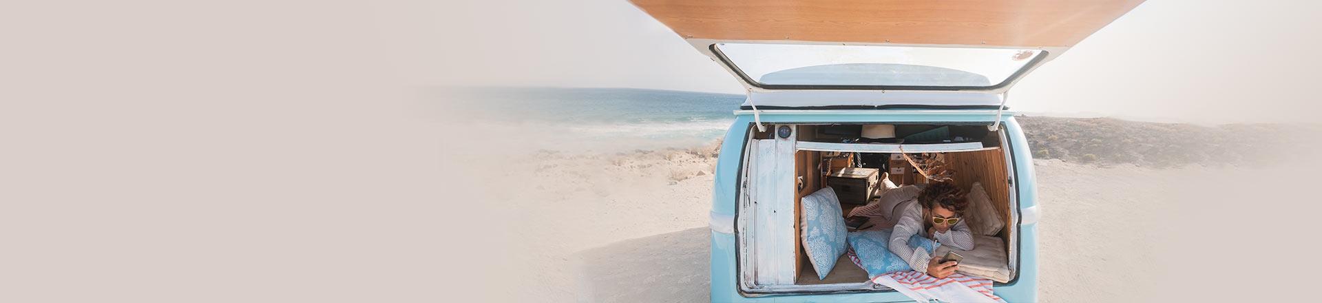 Reise-App: Mann im Auto am Strand